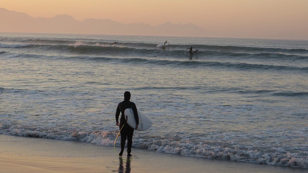Neoprene top to toe, heading into the chilly waves for a misty morning surf at Muizenberg beach in Cape Town, South Africa.