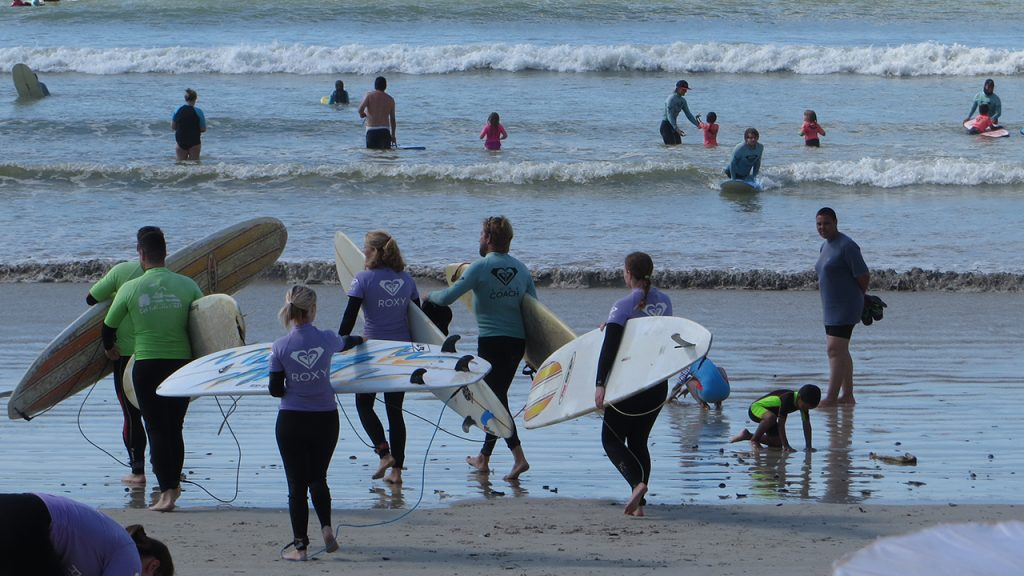 A beginner group of surfers carrying their boards to the water at Muizenberg beach, Cape Town, South Africa.